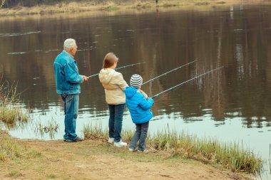 Grandfather and grandchildren are fishing