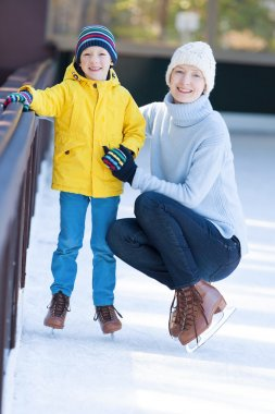 Young mother teaching her positive son ice skating, enjoying winter time at outdoor skating rink together stock vector