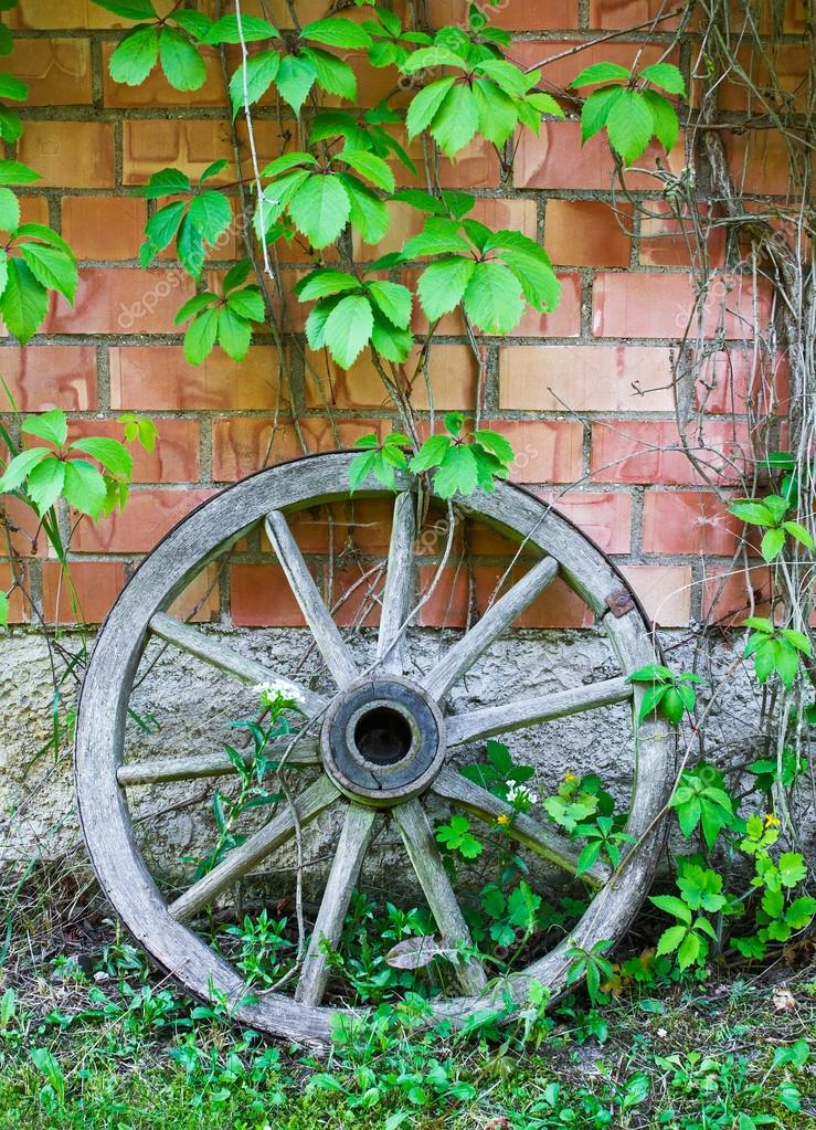 old wooden cart wheel against wall