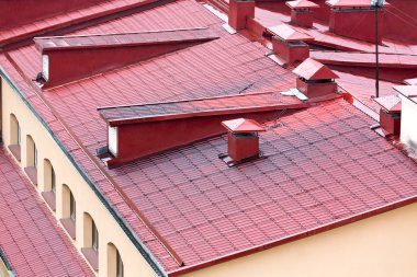 tiled red metal roof with chimneys and windows
