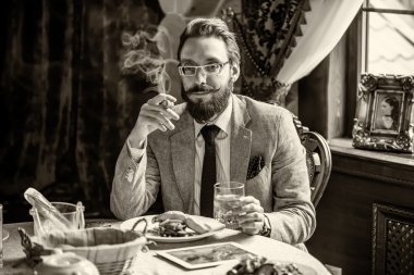 Man with a beard and mustache, smoking a cigar during dinner
