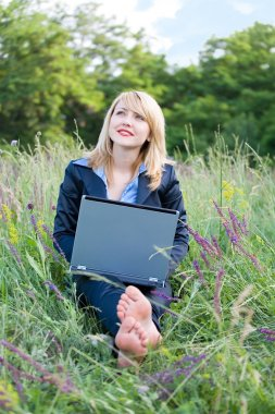 Businesswoman on grass with laptop and take off shoes