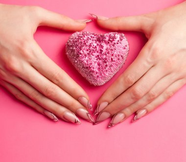 Human hands with beautiful manicure folded in the shape of heart