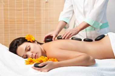 Woman getting a hot stone massage at spa salon