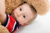 Photo Little boy lye on white bed and embrace toy bear