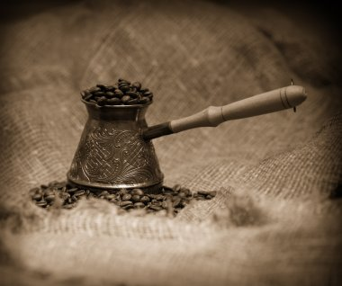 Sepia toned image of cezve with freshly roasted coffee beans