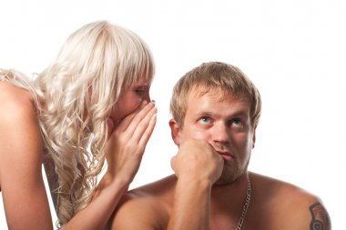 Displeased man listening secret which a female is whispering