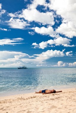 Man relax on sand at lonely beach