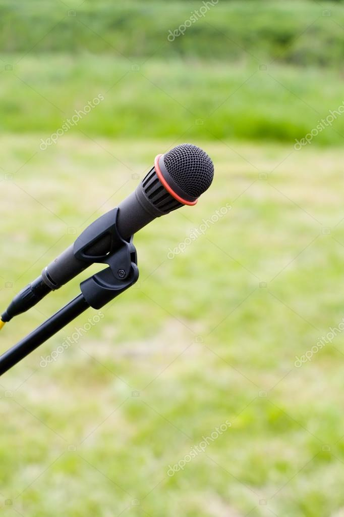 Microphone on air over green grass
