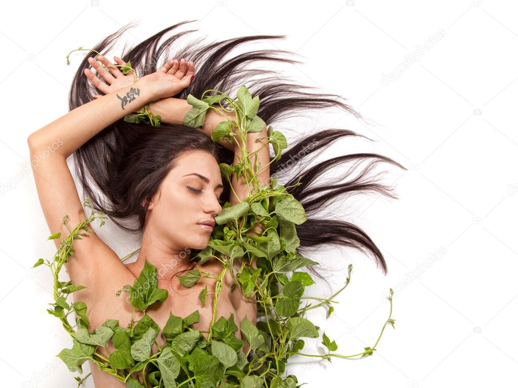 Young beautiful nude woman with green ivy leaves wrapped around
