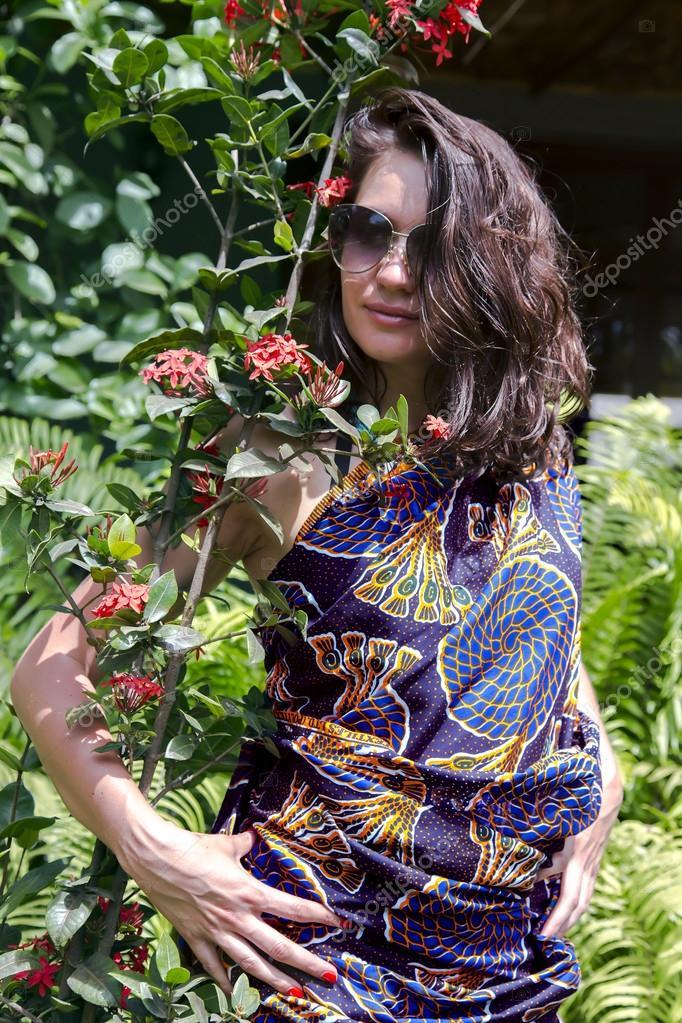 Beautiful brunette in a bright sundress of African motifs