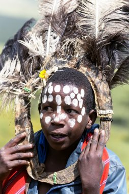 African children with ostrich feather headdress  and painted markings of face