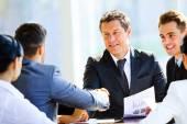 Obchodní přátelé sedí u stolu při setkání s dvěma mužské vedení potřesení rukou