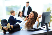 Photo Photo of smiling brunette businesswoman with legs on the desk ph