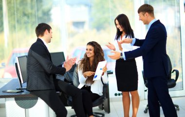 Young businesspeople clapping for female colleague after present