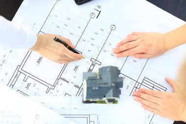 Image of new model house on architecture blueprint plan at desk