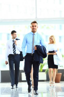 businesspeople group walking at modern bright office interior