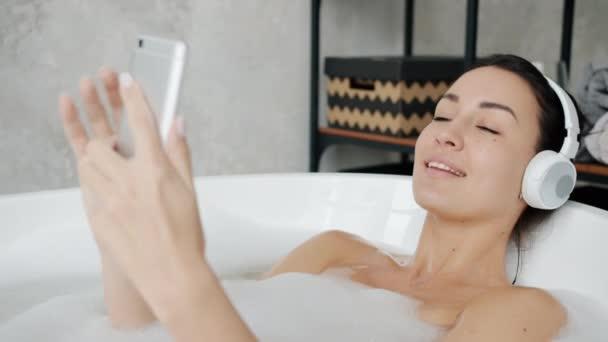Vidám diák visel fejhallgató zenét hallgatni és megérinteni okostelefon képernyő kádban
