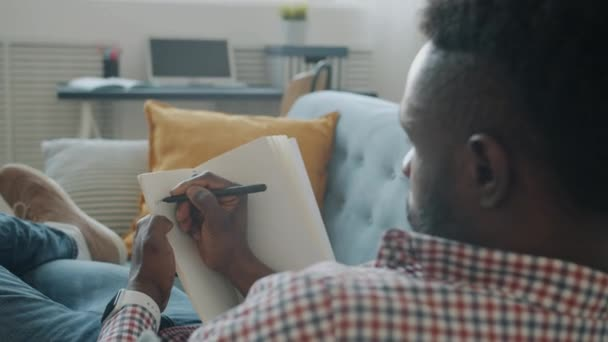 Afroamerikaner macht sich Notizen in Notizbuch, sitzt zu Hause auf Couch