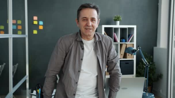 Portrait of cheerful mature businessman standing indoors in workplace smiling looking at camera
