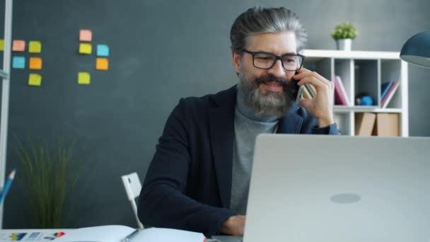 Veselý dospělý muž mluví na mobilním telefonu pomocí notebooku a psaní v notebooku v kanceláři