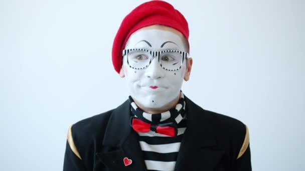 Félénk pantomim művész színes ruhák és szemüvegek nevetés borító száj kézzel nézi a kamera