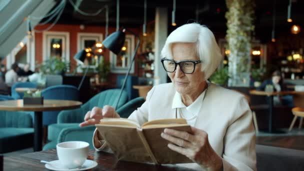 Chytrý senior obchodní dáma čtení knihy u stolu v restauraci relaxaci během přestávky na kávu
