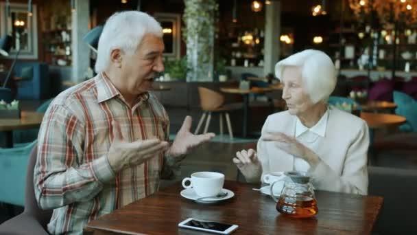 Šťastný starý pár muž a žena mluví dělá high-five gesto ruky a pití čaje v kavárně