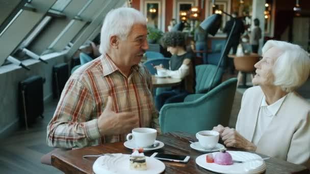 Starší dáma dostává dárek v krásné krabici při romantické večeři v restauraci