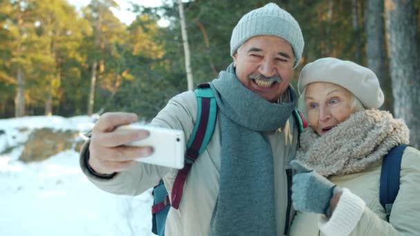 Starší pár se selfie venku v zimní den s úsměvem ukazující palce nahoru pomocí smartphone kamery