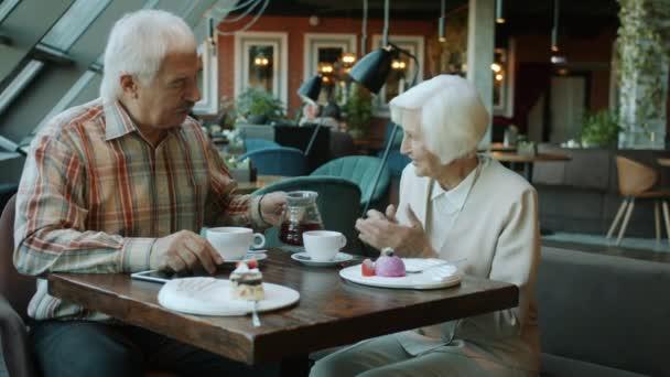 Starší muž nalévání čaje v manželském poháru starat se o ženy mluvit a usmívat se v kavárně