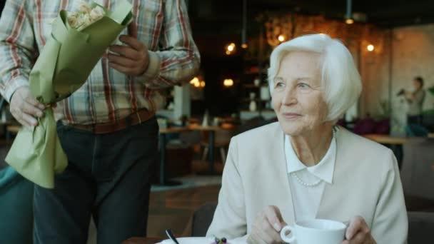 Portrét starší ženy, jak dostává květiny od milujícího muže při večeři v restauraci
