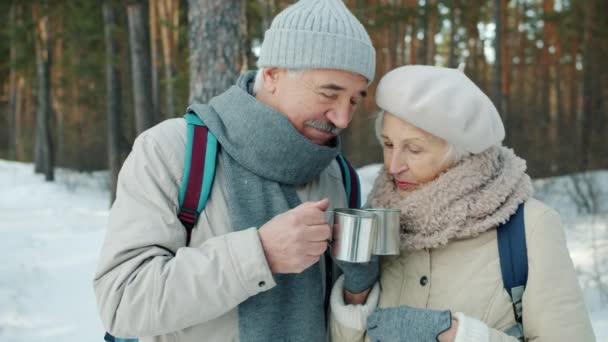 Happy family senior man and woman clanging metal cups and drinking outdoors in winter wood