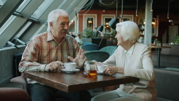 Usmívající se muž a žena stáří mluví a pije čaj v moderní kavárně
