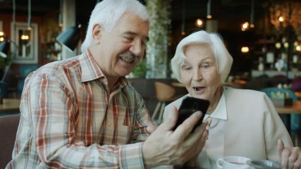 Zpomalený pohyb starších párů muž a žena při pohledu na obrazovce smartphone mluvit a smát se v kavárně