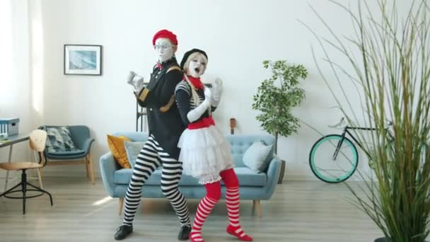 Radostná dívka a chlap napodobuje tanec baví dělat legrační triky uvnitř bytu