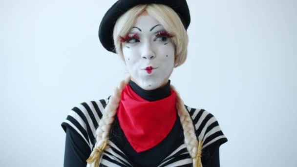 Portré gyönyörű lány pantomim, hogy vicces arcok és mosolygós fehér színű háttér