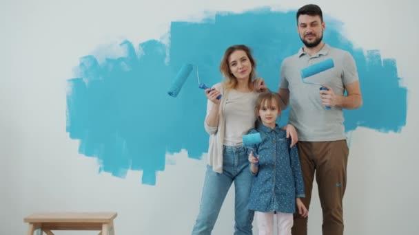 Zpomalený film portrét šťastné rodiny matka otec a dcera drží malířské válce doma