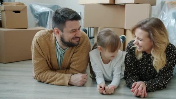 Šťastná rodina žena muž a holčička mluví ležící na podlaze nového domu drží klíč