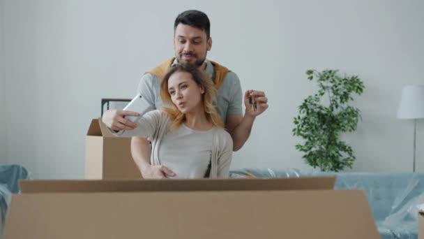 Lassú mozgás boldog pár csinál szelfi új lakás gazdaság kulcs csók pózol okostelefon kamera