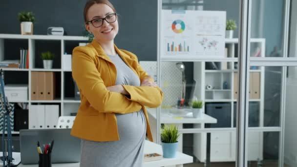 Portrét těhotné mladé podnikatelky stojící v úřadu se zkříženýma rukama s úsměvem