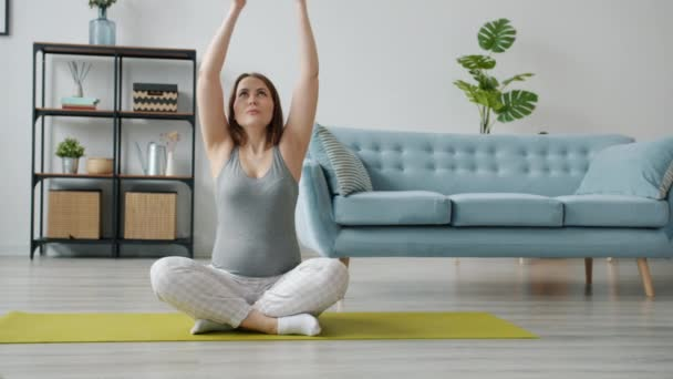 Pregnant girl sitting in lotus position on yoga mat breathing relaxing enjoying peace and tranquility