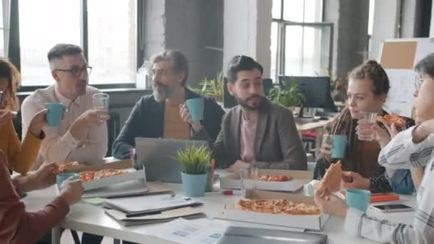 Podnikatelé si užívají pauzu na oběd v práci, jedí pizzu a pijí v kanceláři.