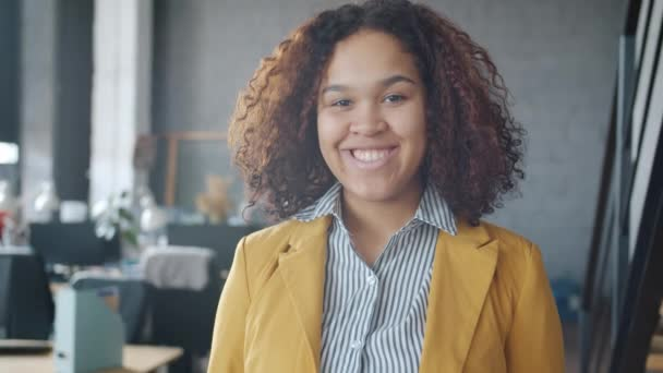 Portrait of joyful mixed race woman standing in office smiling looking at camera