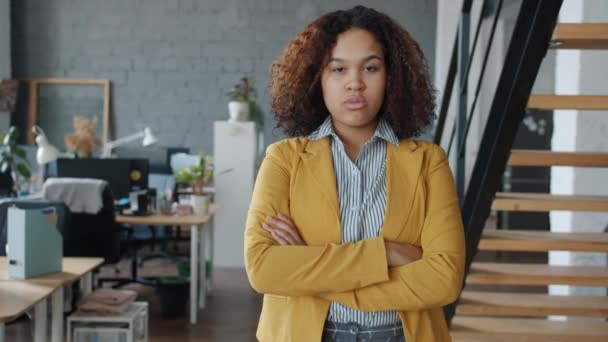 Portrait of ambitious Afro-American businesswoman standing in office with arms crossed