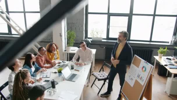 Vysokoúhlý pohled zkušeného podnikatele na prezentaci pro kolegy v úřadu
