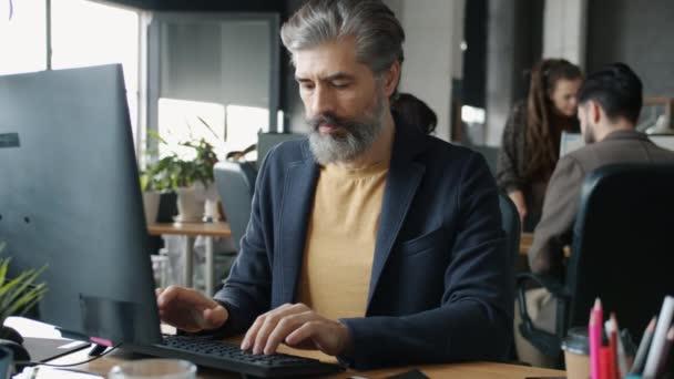 Starší kancelářský pracovník psaní při pohledu na monitor počítače a usmívání ve sdílené kanceláři