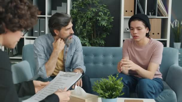 Teenage boy talking to therapist during session with father in modern office