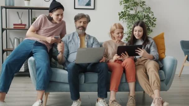 Eltern und Kinder mit Laptop und Smartphone sitzen zu Hause auf der Couch und unterhalten sich