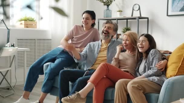 Glückliche Familienmutter Vater Tochter und Sohn fernsehen und zu Hause lachen